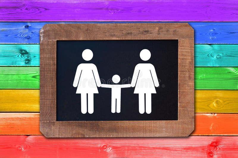 Lesbian family with child white sign on a blackboard, rainbow gay flag wood planks background royalty free stock photography