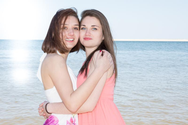 Lesbian lgbt couple looking at the sun while hugging each other on beach stock photos