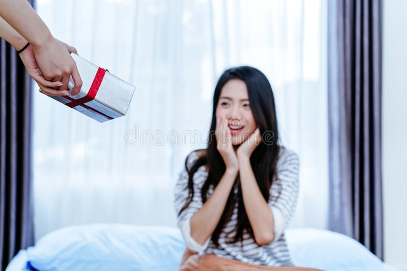 Lesbian LGBT couple surprise with Gift box give to girlfriend. On bed at morning in bedroom after waking up stock image