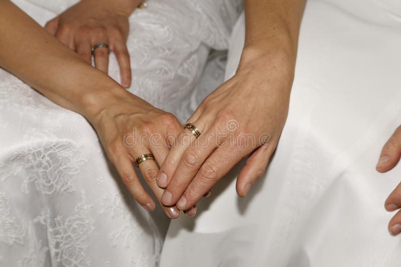 Lesbian wedding. Couple holding hands with rings royalty free stock photos