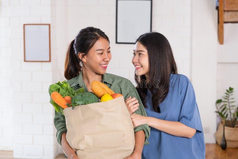 Lesbiana asiática feliz de los pares que celebra el bolso vegetal después de hacer compras en el colmado en casa Concepto de la f imagen de archivo libre de regalías