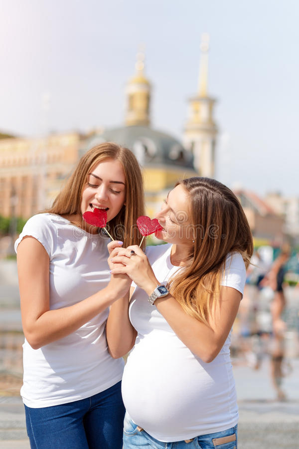 Lesbians mothers, pregnant couple, happy samesex family in the city park at summer. Women eating sweets, heart shaped. Candies, symbol of love royalty free stock photos