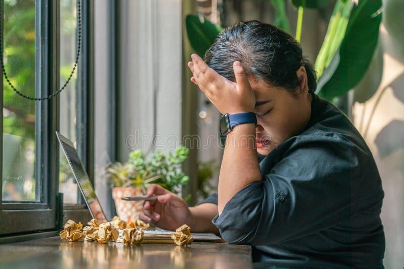 Lesbica asiatica stressante che lavora al computer portatile accanto alla finestra fotografia stock libera da diritti