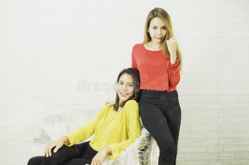 Lesbiennes lesbiennes asiatiques des femmes LGBT utilisant les chemises jaunes et rouges, longs cheveux, poses de courrier, prena image stock
