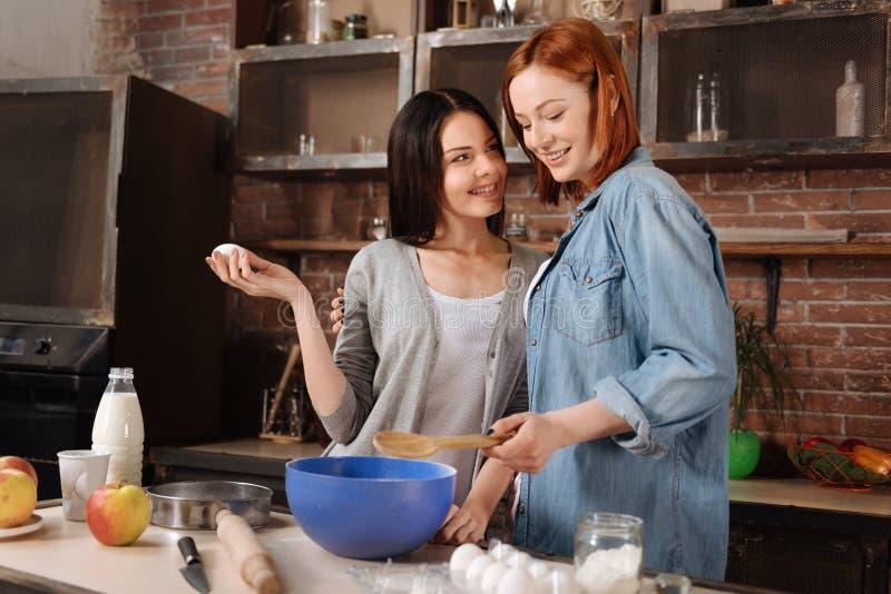 Lesbiennes avec plaisir positives tout en faisant cuire photos stock