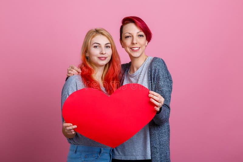 Lesbiennes die en een groot hart op een roze achtergrond koesteren houden stock fotografie