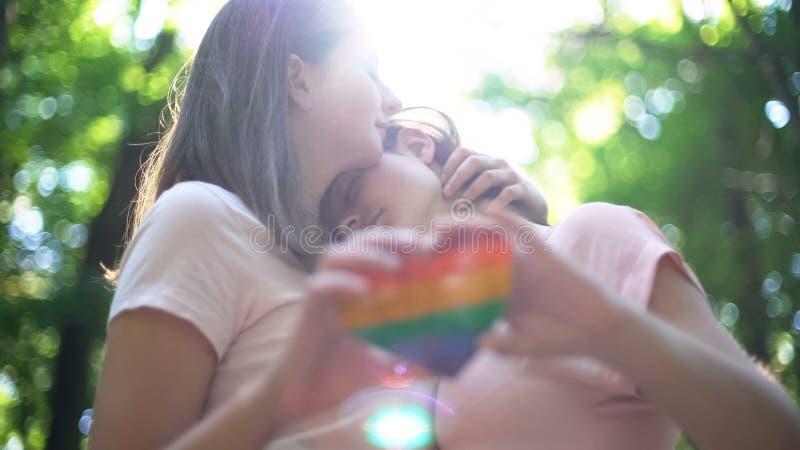 Lesbiennes in liefde omhelzen, die regenbooghart, concept houden lgbtrechten stock afbeelding