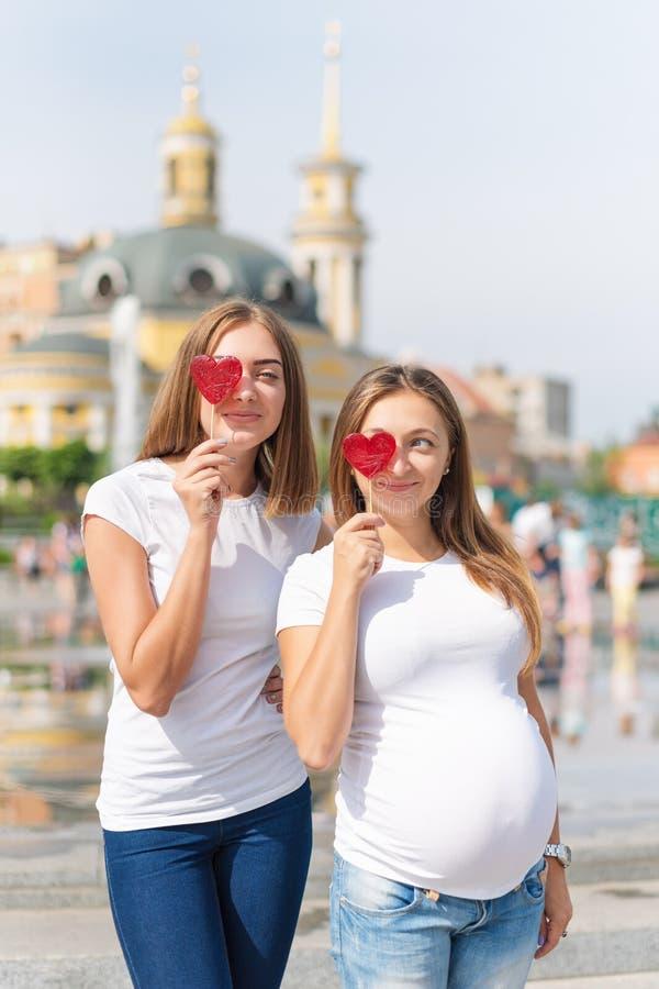 Lesbiennesmoeders, zwanger paar, gelukkige samesexfamilie in het stadspark bij de zomer Vrouwen die snoepjes, gevormd hart houden royalty-vrije stock fotografie