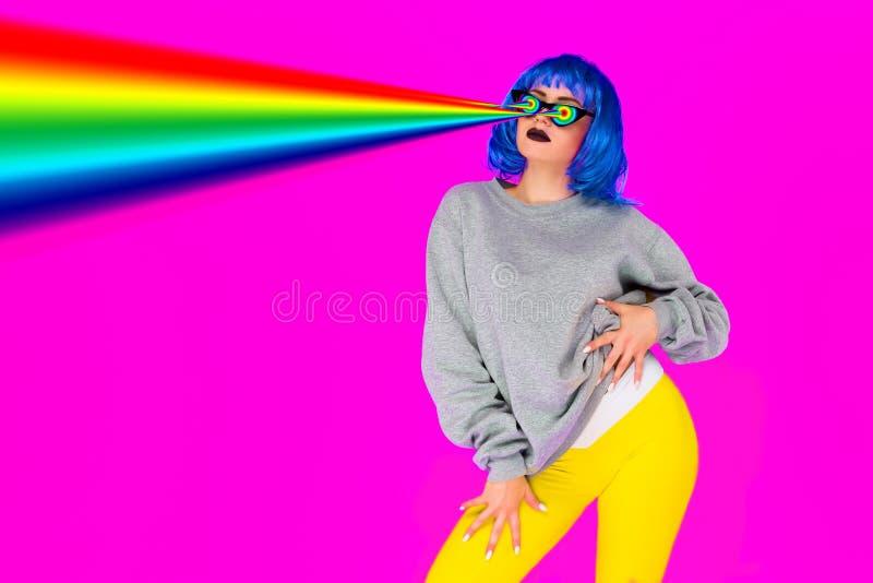 Lesbijska dziewczyna w błękitnych peruki i okularów przeciwsłonecznych krótkopędach od jej oko tęczy laserów na różowym tle obrazy royalty free