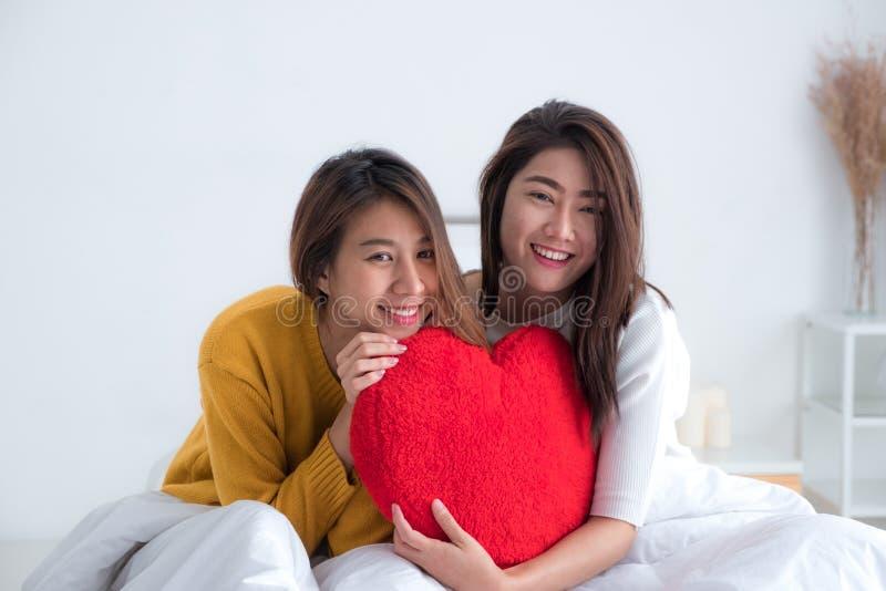Lesbisch lgbtpaar die van Azië rood harthoofdkussen samen en s houden royalty-vrije stock afbeelding