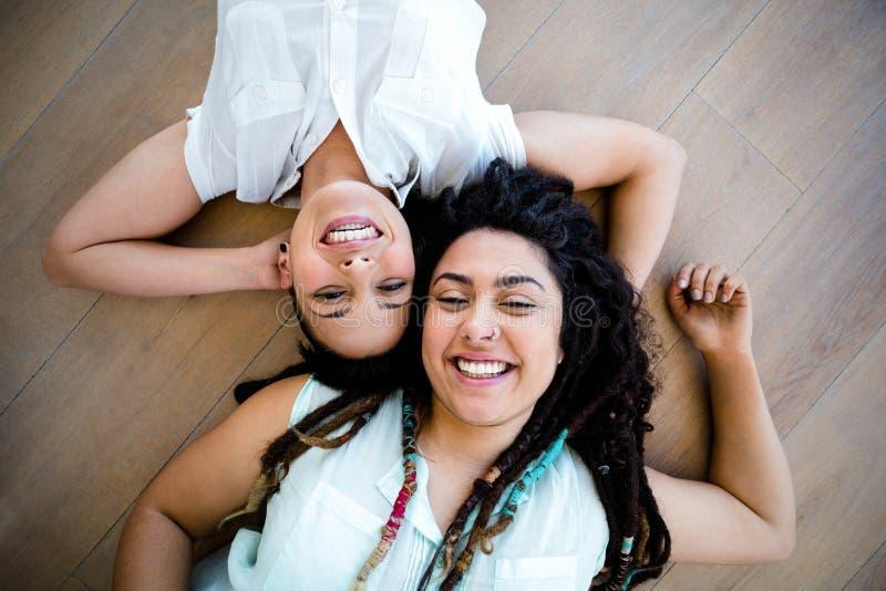 Lesbisch paar die op vloer liggen stock afbeeldingen
