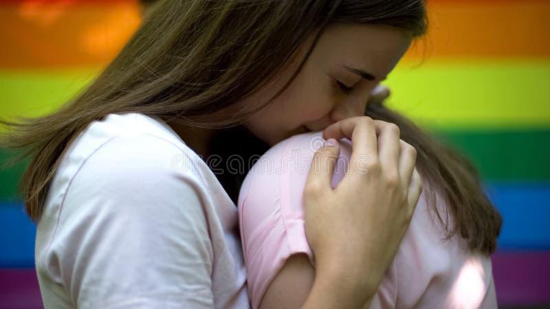 Lesbisch paar die teder, openbaar gevoel, zelfde-geslachtsliefde uitdrukken omhelzen die stock foto's