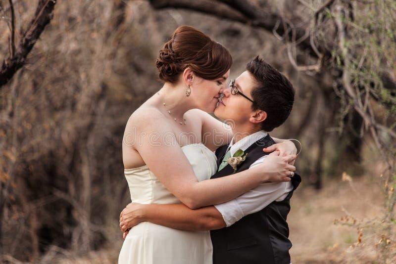 Lesbische Paare, die im Holz küssen stockbilder