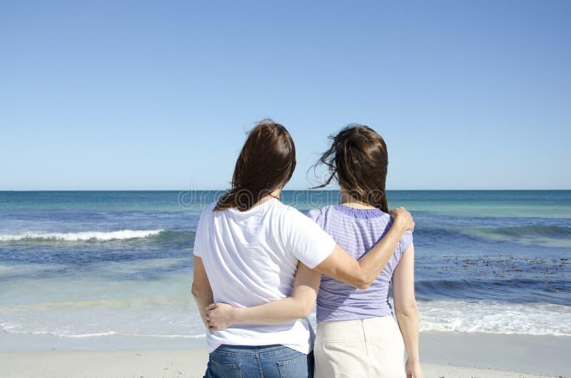 Lesbische Paare, die zusammen in Ozean stehen lizenzfreies stockbild