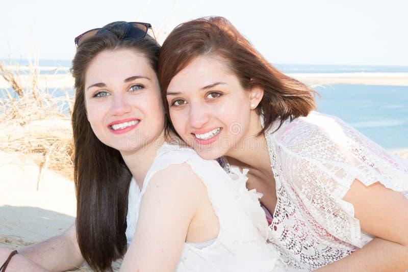 Lesbische Paarstellung am Strand in der Liebe, die Kamera untersucht lizenzfreie stockfotografie