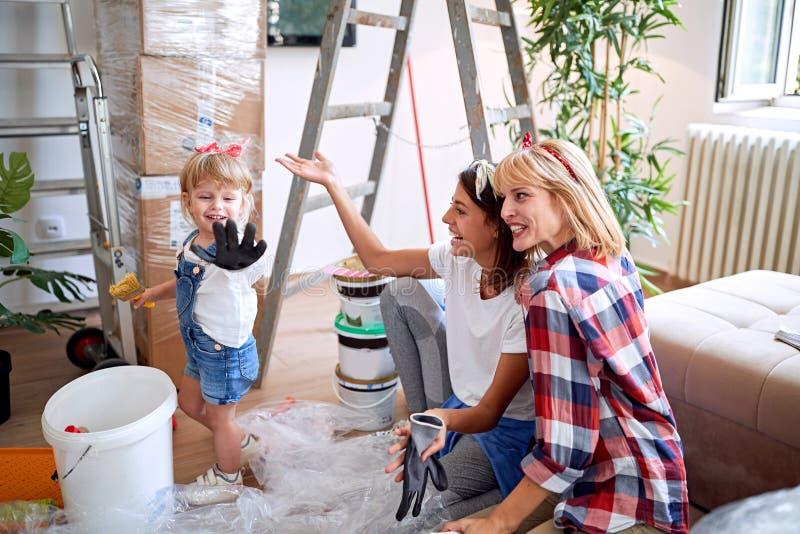Lesbische paarvrouwen die zich in nieuw huis bewegen en pret met een peutermeisje hebben stock afbeelding