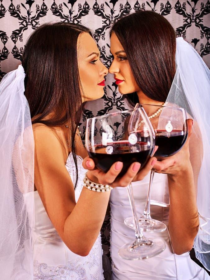Lesbische paren in huwelijks bruids kleding die en rode wijn kust drinkt royalty-vrije stock afbeeldingen