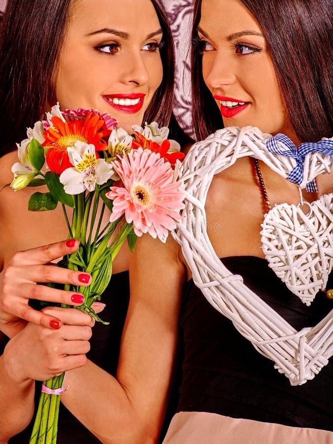 Lesbische vrouwen met hart en bloemen stock foto's