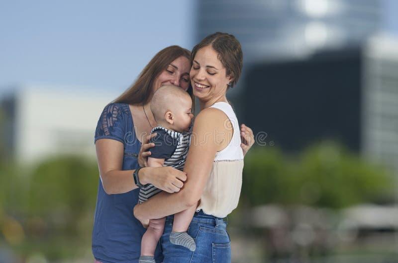 Lesbisk förälskelse, unga lesbiska mödrar med deras behandla som ett barn homosexual royaltyfri fotografi