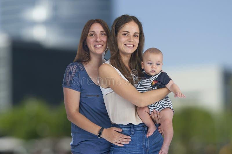 Lesbisk förälskelse, unga lesbiska mödrar med deras behandla som ett barn homosexual arkivbilder