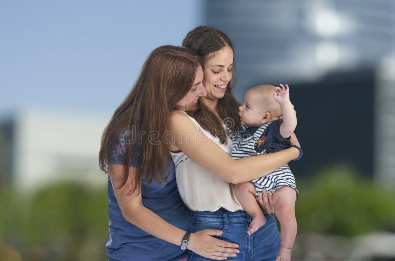 Lesbisk kärlek, unga lesbiska mödrar med sitt barn Homosexuella royaltyfri foto