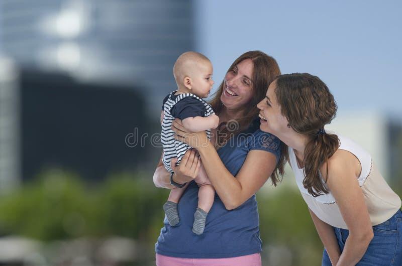 Lesbiska mödrar med deras behandla som ett barn Homosexuell familj, lesbisk förälskelse arkivfoton