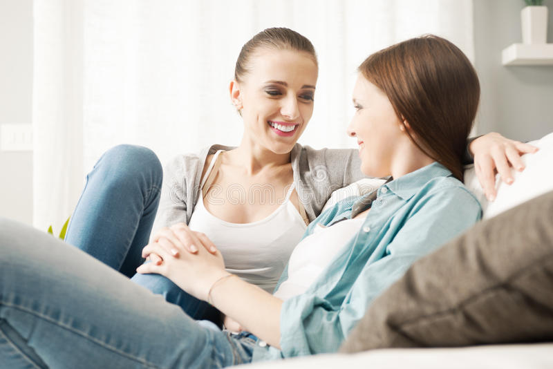 Lesbiska par som hemma flörtar royaltyfri fotografi