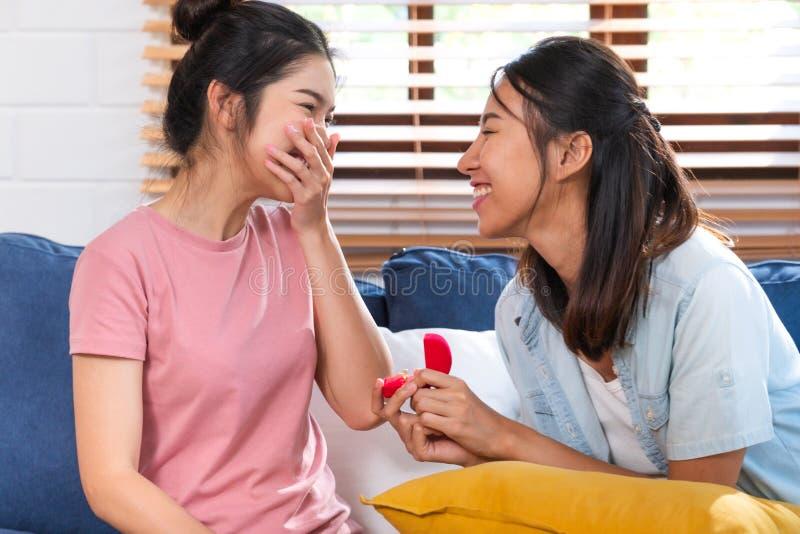 Lesbiskt förslag för lyckliga asiatiska par med cirkeln för att att gifta sig på vardagsrum hemma LGBTQ-livsstilbegrepp royaltyfri fotografi