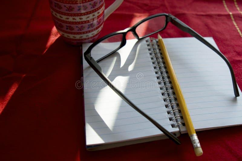 Lesebrille mit Notizbuch und Bleistift auf einer Tabelle lizenzfreie stockbilder