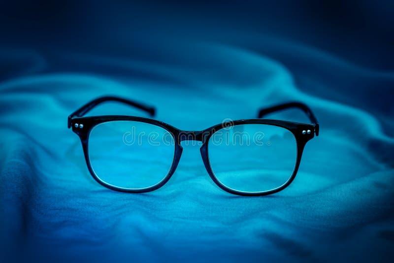 Lesebrillen auf blauem Gewebehintergrund lizenzfreie stockfotografie