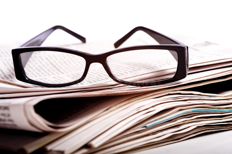 Lesegläser auf Zeitungen stockbild