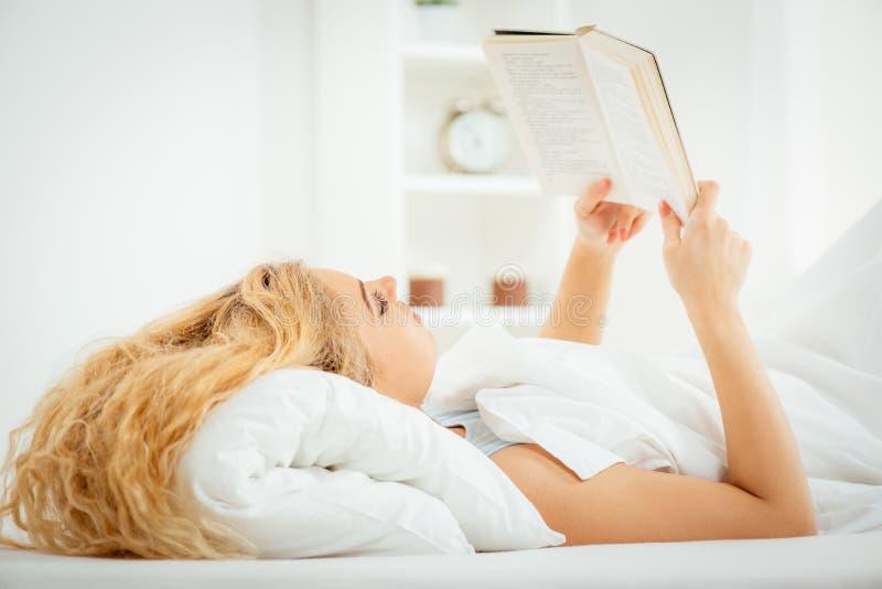 Lesen im Bett lizenzfreie stockfotos