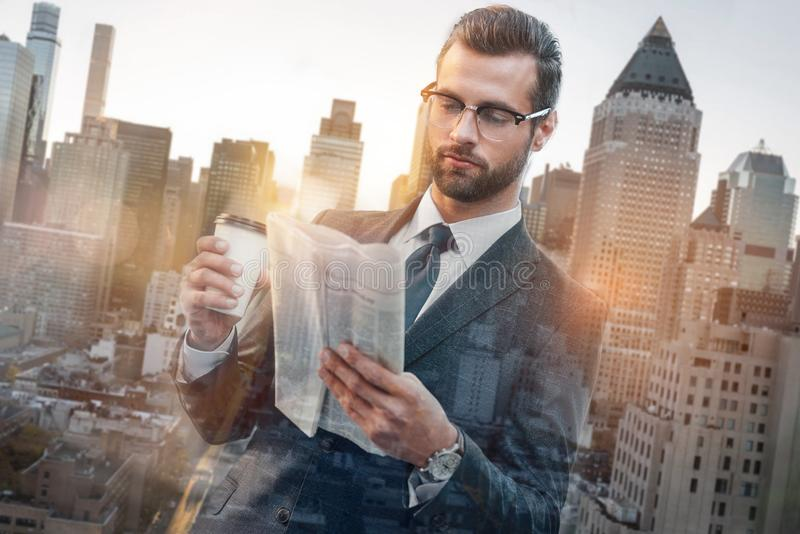 Lesenachrichten Überzeugter junger Geschäftsmann in der Klagenlesezeitung und im halten Tasse Kaffee bei draußen stehen stockbilder