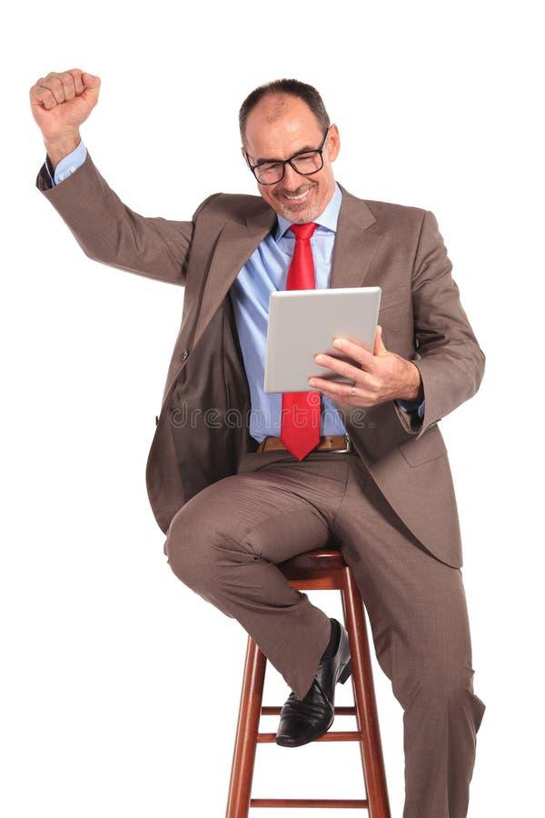 Lesende gute Nachrichten des alten Geschäftsmannes auf Tablette stockfotos