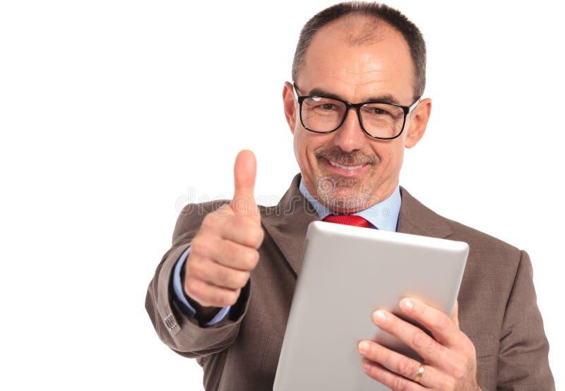 Lesende gute Nachrichten des glücklichen älteren Geschäftsmannes auf seiner Tablettenauflage stockbilder
