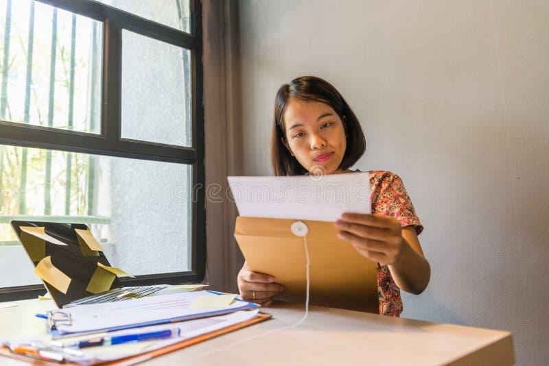 Lesender Finanzdokumentenbericht der jungen Bürofrau stockbilder