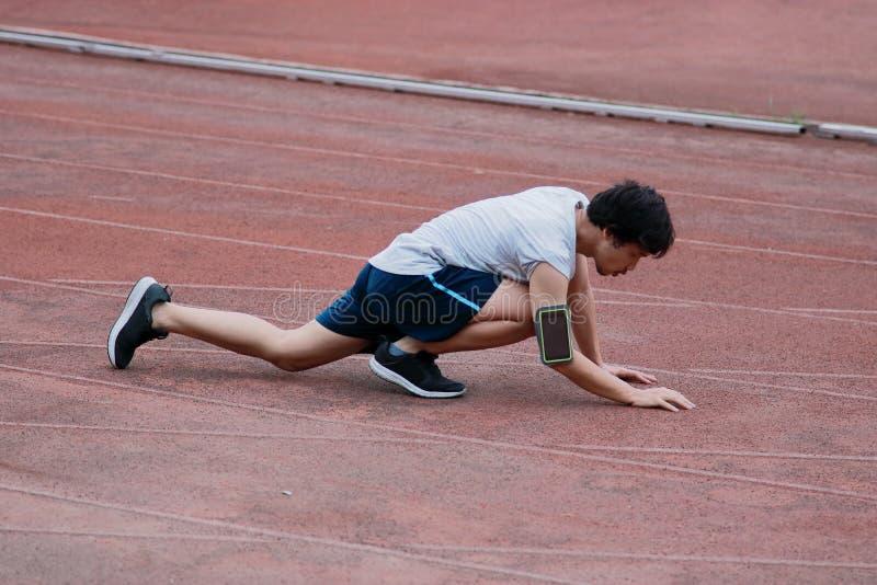 Lesión asiática joven del corredor y el acostarse en pista durante el funcionamiento Concepto del deporte del accidente fotografía de archivo libre de regalías