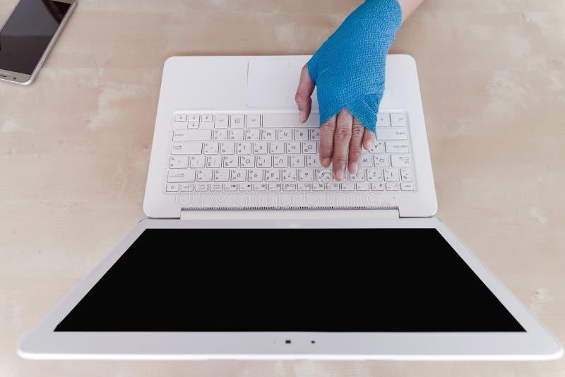 Lesión de trabajo  dolor herido de la mano de la mujer con el vendaje elástico azul o foto de archivo libre de regalías