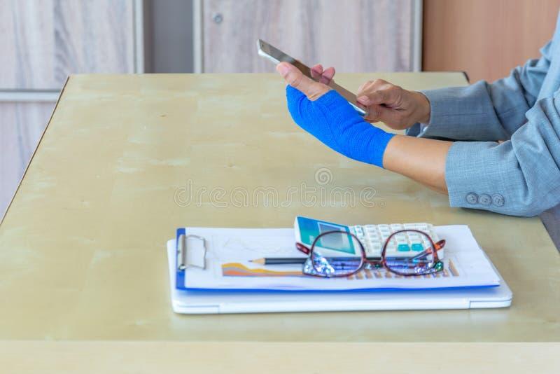 Lesión de trabajo  dolor herido de la mano de la mujer con el vendaje elástico azul o imagenes de archivo