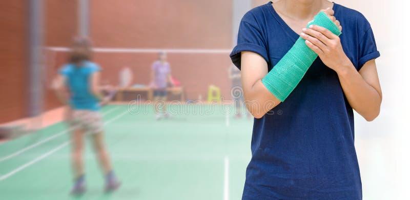 lesión del deporte, jugador de la mujer con el molde verde del brazo en b borroso fotos de archivo libres de regalías