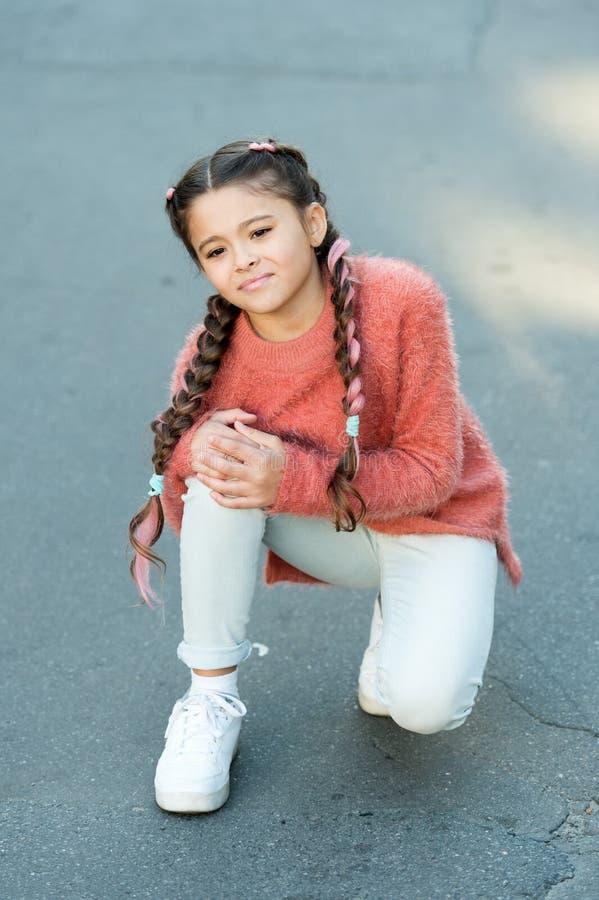 lesión en la pierna de la niña El pequeño niño tiene dolor en rodilla niña de grito en suéter del otoño El otoño se acurruca Otoñ fotografía de archivo