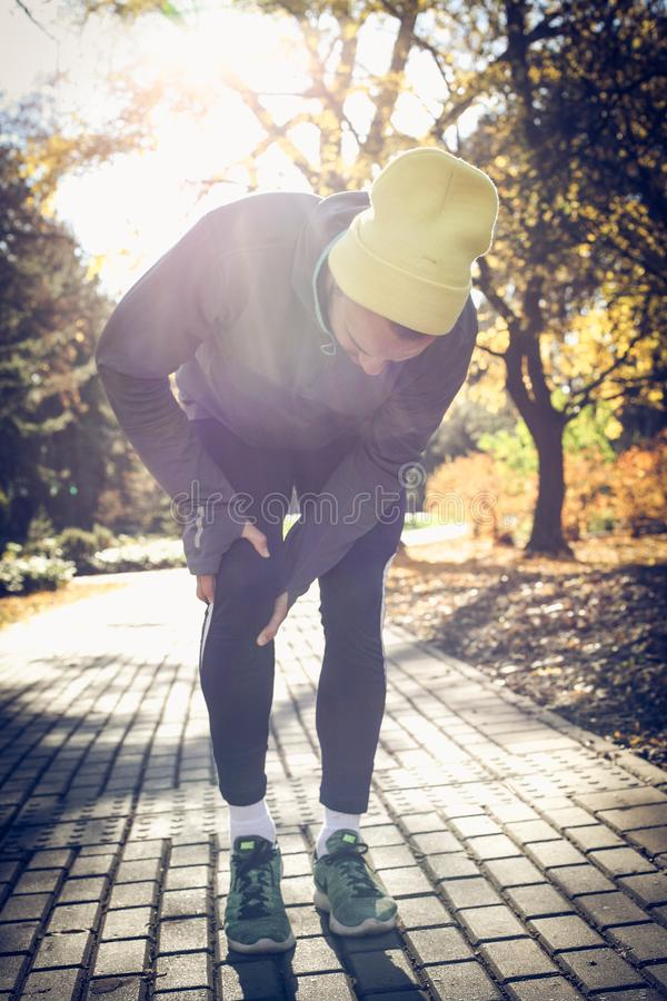 Lesión en rodilla es dolorosa Hombre joven imagen de archivo