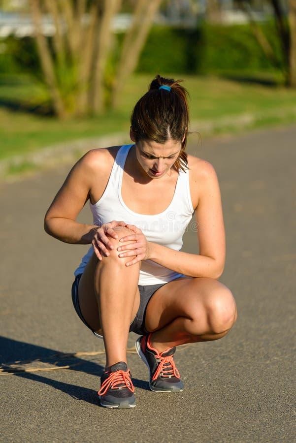Lesión sufridora del deporte de la junta de rodilla del atleta de sexo femenino fotografía de archivo libre de regalías