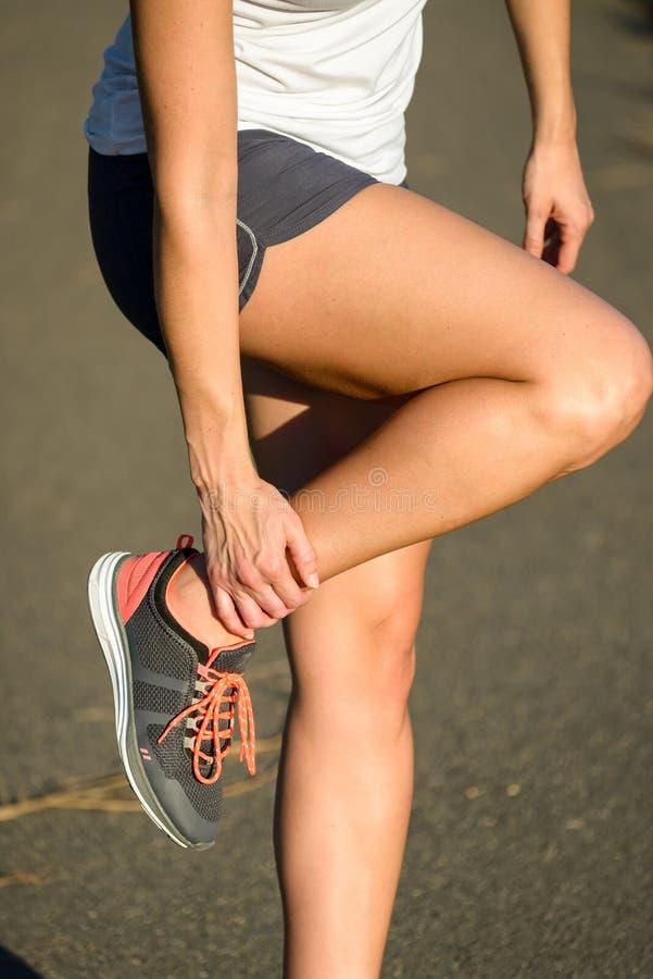 Lesión sufridora del deporte del esguince del tobillo del corredor femenino fotografía de archivo