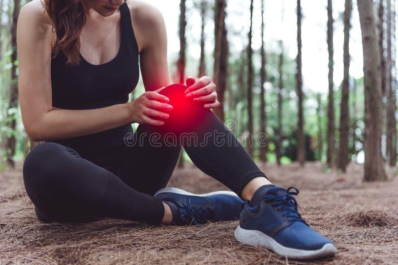 Lesi?n de la mujer del deporte en la rodilla durante activar en fondo de maderas de pino del bosque Concepto m?dico y de la atenc fotos de archivo