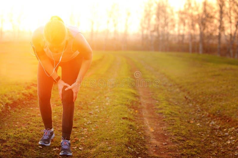 Lesiones - deportes que corren la lesión de rodilla en mujer imagen de archivo