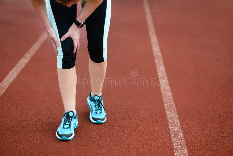 Lesiones - deportes que corren la lesión de rodilla en mujer imagen de archivo libre de regalías