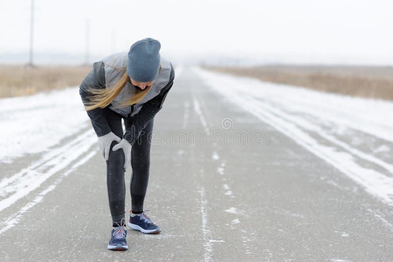 Lesiones - deportes que corren la lesión de rodilla en mujer Maratón del invierno imagen de archivo libre de regalías