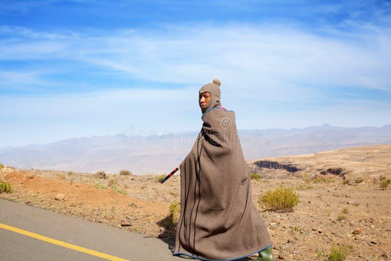 Lesotho, Afrikaanse jonge herdersmens in nationale wol algemene kleding en balaclava GLB gaat langs landelijke hoge bergweg, blau stock afbeelding