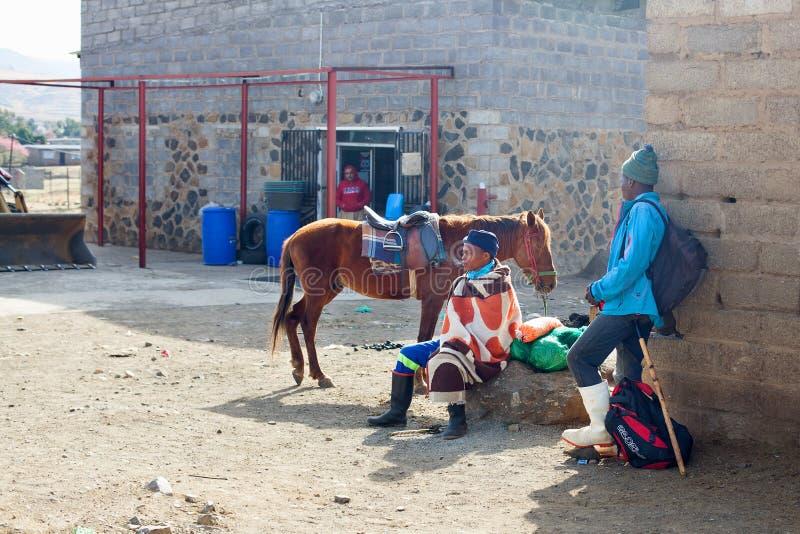 Lesoto, homem africano novo do pastor no vestido geral de lã nacional senta-se na pedra grande com amigo e cavalo na rua rural da imagens de stock